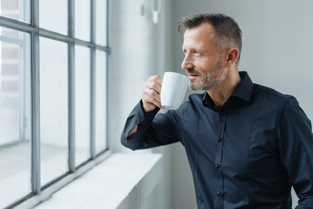 Portrait of a confident middle-aged man daydreaming about future while drinking coffee at the window during break at work in the office