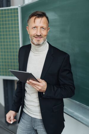 Portrait of a confident middle-aged teacher looking at camera while holding a tablet pc in the classroom in a modern school