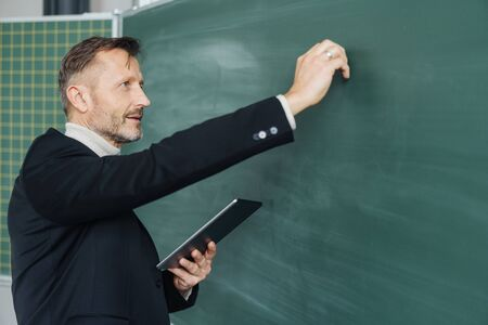 Middle-aged male teacher writing on a blank chalkboard while holding a tablet computer in his hand