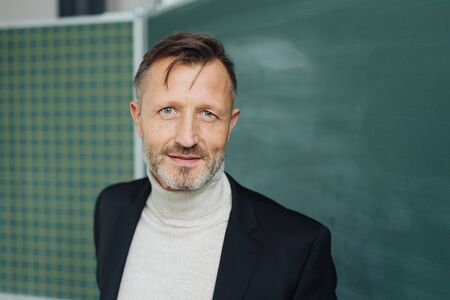 Professor or male teacher in a classroom standing in front of a chalkboard looking into the camera with a thoughtful expression Banque d'images