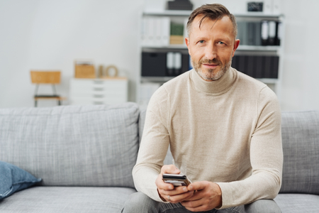 Attractive mature bearded man relaxing at home on a couch sitting holding a smartphone looking thoughtfully at the camera with copy space