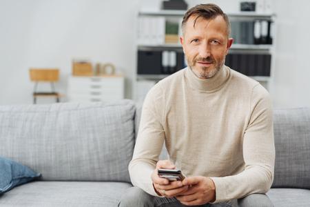Uomo barbuto maturo attraente che si rilassa a casa su uno strato che si siede tenendo uno smartphone che esamina meditatamente la macchina fotografica con lo spazio della copia Archivio Fotografico - 94792430