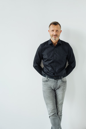 Studio shot portrait of a middle-aged confident man smiling while wearing cool casual clothes as gray jeans and black shirt
