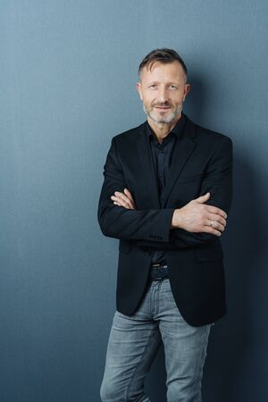 Confident middle-aged man in jeans and jacket standing with folded arms against a dark studio background with copy space