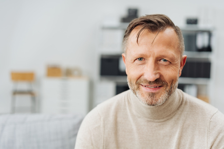 Happy successful businessman with a friendly smile relaxing at the office in a close up head and shoulders with copy space
