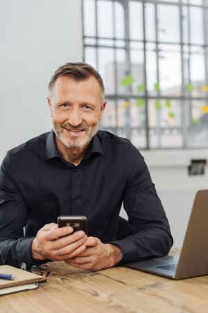 Smiling pleased businessman holding a mobile phone as he sits working at a laptop in his office
