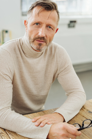 Concerned man with an earnest expression staring intently at the camera as he sits at a table holding his glasses Stock Photo