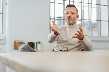 Middle-aged man sitting explaining something gesturing with his hands in a low angle view over a table with copy space