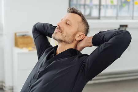 Businessman relaxing with his eyes closed and hands clasped behind his neck as he sits back in his chair Stock Photo