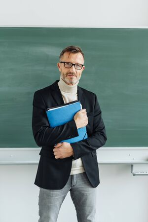 Confident smart male teacher or professor standing in front of a blank chalkboard in a classroom clutching a folder of notes to his chest