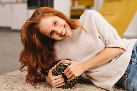 Smiling young attractive redhead woman relaxing on a carpet in her living room at home looking at the camera with a vivacious cheeky grin