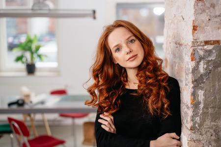 Poważna piękna, uważna młoda ruda kobieta oparta o ceglaną ścianę wewnętrzną wpatrując się w kamerę