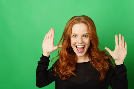 Vivacious extrovert young redhead woman having fun laughing at the camera while holding up her hands over a green studio background with copy space