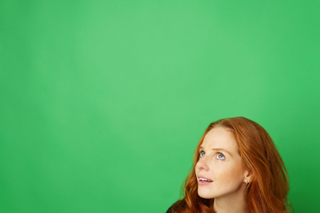 Thoughtful young redhead woman looking up towards large blank copy space on a green studio background