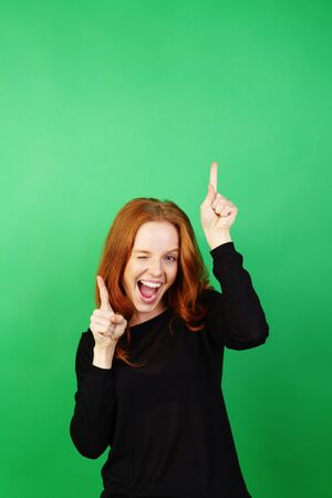 Portrait of young happy red-haired enthusiastic woman standing against green background