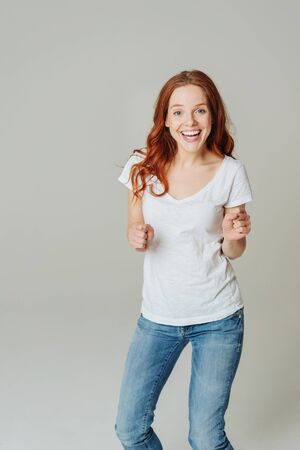 Motivated happy young redhead woman in a casual white top and jeans standing grinning happily at the camera over a neutral studio background