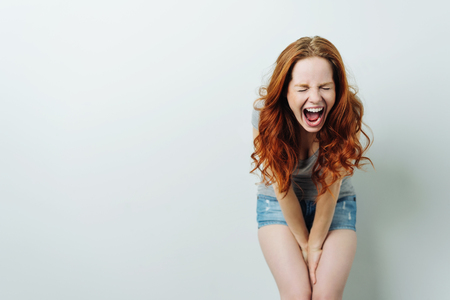 Stressed out young woman wearing denim shorts leaning forward screaming in frustration with copy space