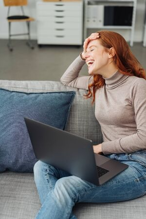 Young red-haired woman laughing while sitting on sofa with laptop