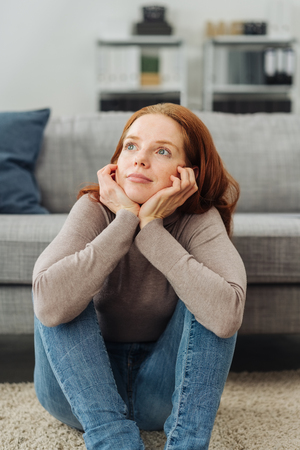 Young red-haired thoughtful woman with head in hands sitting on carpet at home