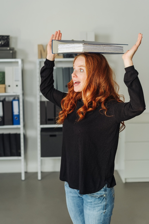 Cute young redhead woman balancing a file or binder full of papers on her head with a look of excited astonishment in a spacious office Foto de archivo