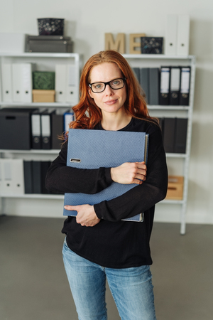 Casual young businesswoman or student in denim jeans and glasses standing clutching a large office binder to her chest as she stares thoughtfully at the camera 스톡 콘텐츠