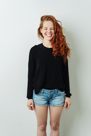 Fun happy young redhead woman wearing trendy skimpy denim shorts standing grinning with her eyes closed over a white studio background