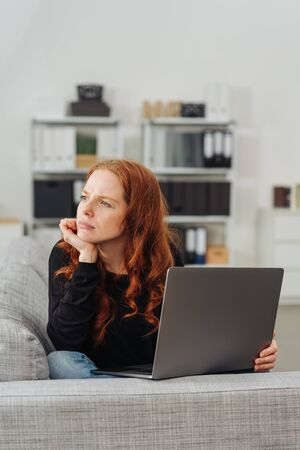 Portrait of young thoughful red-haired woman sitting with laptop on sofa 免版税图像