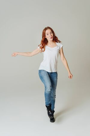Cute playful young redhead woman prancing and smiling in a pair of casual denim jeans and boots over a white studio background
