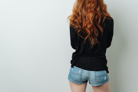 Rear view of a sexy redhead woman with a cute butt in skimpy denim shorts in a close up cropped view over white with copy space