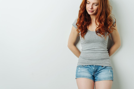 Attractive sexy young woman in denim shorts with a dreamy expression standing looking down to the side in a close up cropped view with copy space
