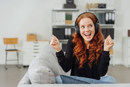 Extrovert young woman singing along to her music as she relaxes on a sofa at home listening on stereo headphones