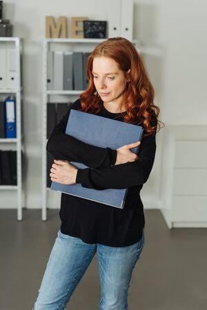 Attractive casual young businesswoman in jeans standing clasping a large office binder to her chest as she looks thoughtfully down at the floor