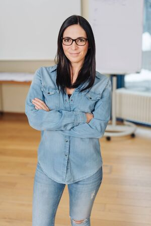 Young cheerful woman wearing glasses standing with arms crossed against whiteboard