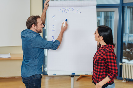 Businessman and woman working on a project together standing making handwritten notes on a flip chart in an office Stock Photo