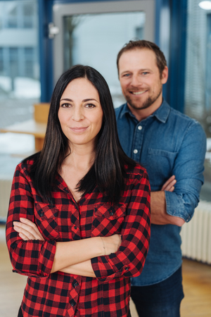Modern casual young business team with a man and woman posing together in a large office smiling at the camera