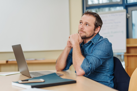 Businessman pondering a problem in the office sitting with his chin on his hands staring upwards with a contemplative expression Stock Photo