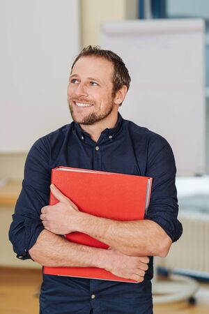 Cheerful man standing with red ring binder in office