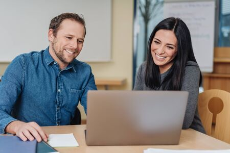 Happy smiling businessman and woman working together on a laptop computer in a modern stylish office Stock Photo