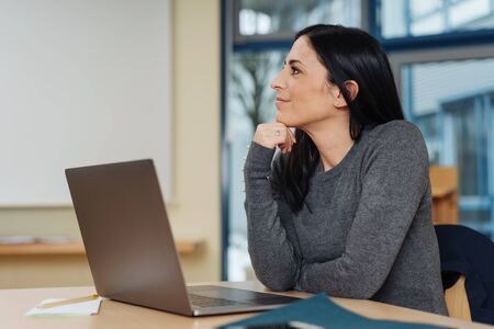 Businesswoman sitting at her desk thinking with her chin on her hand looking to the side in a modern office