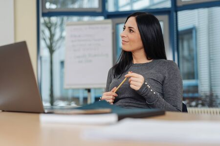 Smiling businesswoman sitting watching to the side in a low angle view over a wooden office table