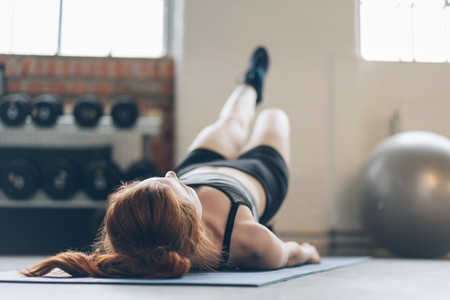 Fit woman doing exercises in a gym lying on her back on a yoga mat with her leg and body raised in a head to toe low angle view Stock Photo