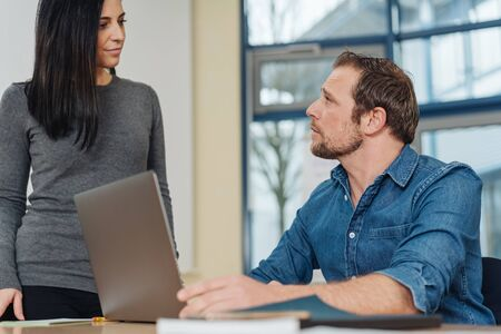 Emotionless man sitting at desk with computer, looking up at his young woman colleague, standing near his desk in office