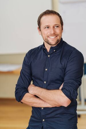 Handsome man in black shirt with rolled up sleeves standing indoors with arms folded and looking away, smiling