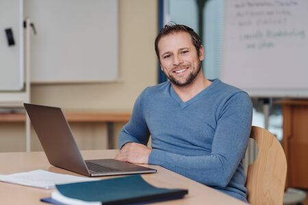 Portrait of cheerful man sitting in front of laptop at office