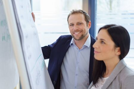 Smiling stylish businessman in a meeting with a female colleague as they stand together at a flip chart doing an analysis Foto de archivo
