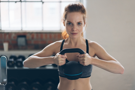 Determined young woman holding a kettle weight in a gym as she works out lifting it to chest height to strengthen her muscles Stock Photo