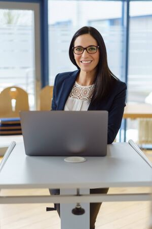 Friendly businesswoman standing at her desk with a laptop computer looking at the camera with a warm smile