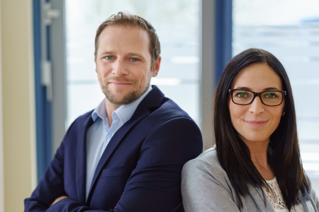 Smart successful business partners, with a smiling man and woman posing side by side against an office window backdrop