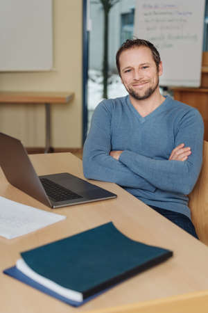 Smiling relaxed businessman with a lovely warm friendly smile sitting at an office table at his laptop with folded arms