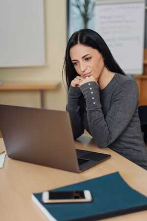 Young long-haired woman sitting at desk in front of computer
